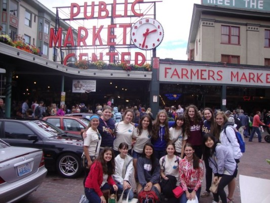 Academt girls stand in from of the famous Pike's Market in Seattle, Washington.