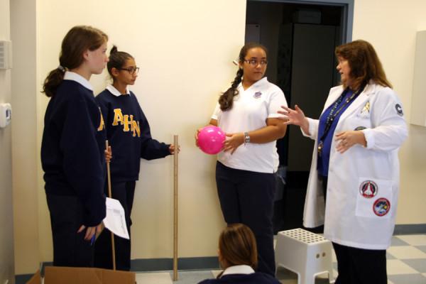 Mrs. Quire guides her freshmen physics class through a lab.