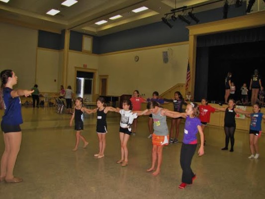 Sophomore Kelsea Henry teaches the little girls how to be in a kick line.