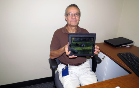 Mr. Ruano displays a photo of some of his current foster children playing with his biological son and his dog.