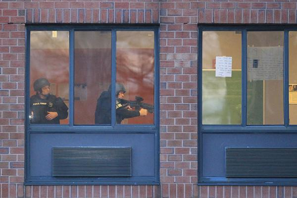 SWAT team members conduct a room-by-room search inside the Delaware Valley Charter High School in Philadelphia, where two students were shot, Friday, Jan. 17, 2014.