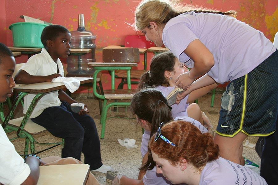 Missionaries fit children for shoes during the DR Trip in 2013