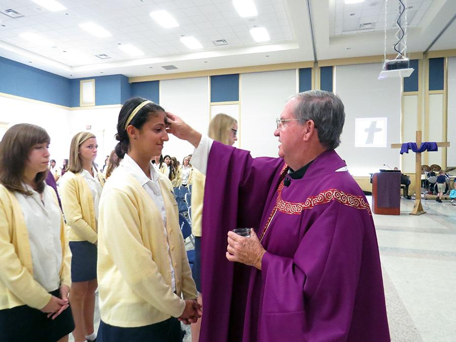 Junior Natalie Smith receives her ashes at Ash Wednesday mass, making the start of her lenten promise, giving up soda.