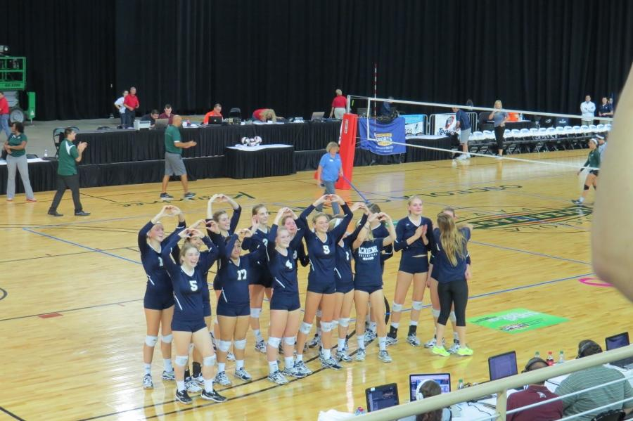 The volleyball team turns to students in the stands while holding up hearts to show their love.