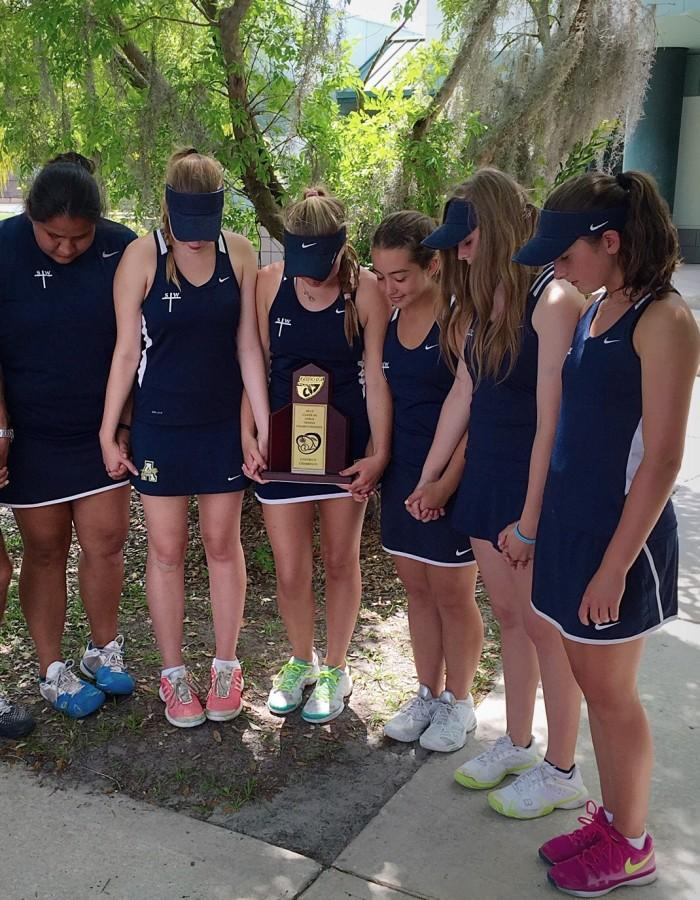 Tennis Team prays to Sydney after clinching the District title.