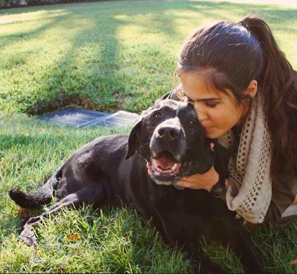 Senior Isabella Alfonso poses with her pup as he smiles at the camera.  Credit: Isabella Alfonso/Achona Online