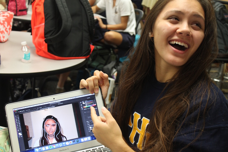 Tess Jakubiec, a student enrolled in AP Art Studio, laughs at how hard it was for her to add bold white lines to an image of herself.
