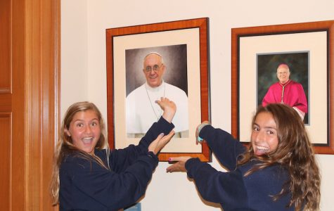 Freshmen Sophia Arnold and Isabella Schellman find inspirational things everyday, including a smiling portrait of our pope on the first floor lobby at AHN.