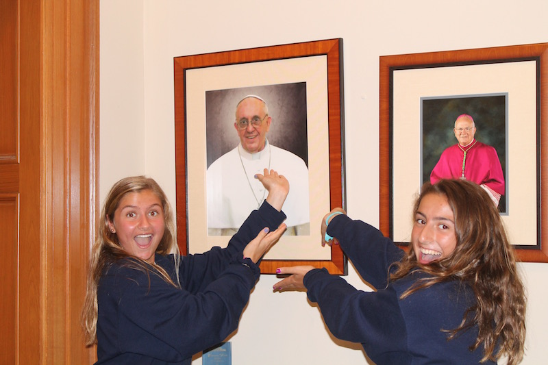 Freshmen+Sophia+Arnold+and+Isabella+Schellman+find+inspirational+things+everyday%2C+including+a+smiling+portrait+of+our+pope+on+the+first+floor+lobby+at+AHN.