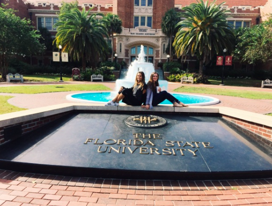 Myah Rhines and Maddie Urso posing in front of the FSU sign on their first day there.
