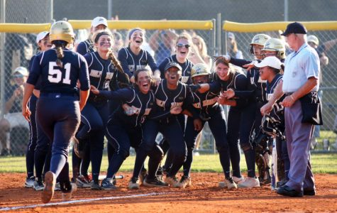The team waits at the plate celebrating Miniet's homerun. Photo Credit: Alexis Miniet (used with permission).