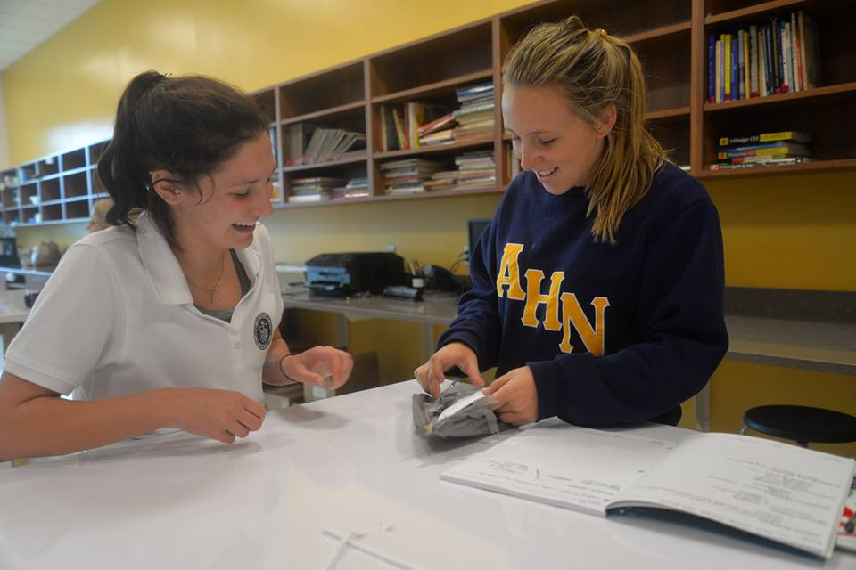 Saragail ('18) and Maddison Troy ('19) are working together to build their paper airplane project project.