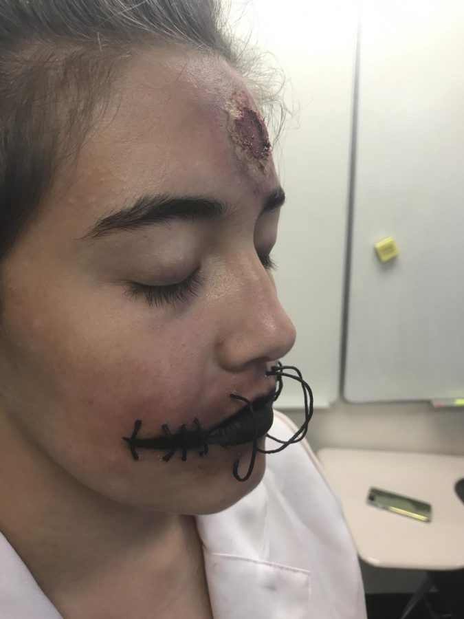 Victoria Fuentes ('20) uses string and Spirit Gum too create a chilling look on her friend. Photo Credit: Olivia Traud/ACHONAOnline