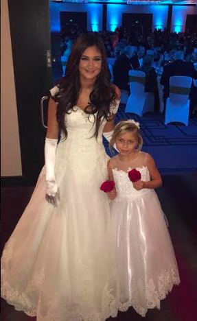 The debutantes walk beside little girls who one day are to be debutantes as well.
