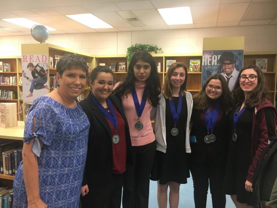 Speech and Debate team members pose with the medals they have won at the Florida Forensic League (Photo Credit: Jamie Meyer, used with permission).