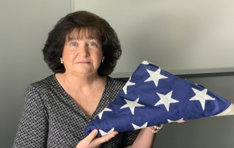 Teacher, Beth Chase, pictured with her beloved American flag which serves as a symbol of her patriotic character.