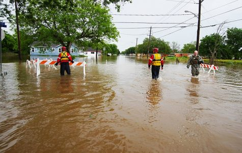 Texas Guardsmen and Texas Task Force 1 rescue personnel wade through thigh-deep water to  help stranded residents back to rescue vehicles during severe flooding in Wharton, Texas, April 21, 2016. In coordination with Texas Task Force 1 and the City of Wharton emergency services, a detachment from Delta Company of the 536th Brigade Support Battalion, Texas Army National Guard deployed several Light Multi-terrain Vehicles to floodwaters rescuing both people and pets. (U.S. Army National Guard photo by 1st Lt Zachary West)