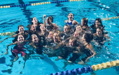 The Academy swim team continues their tradition of jumping into the pool with their trophy after earning the title of regional champions.
