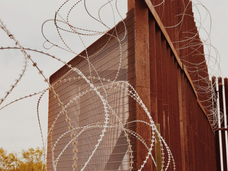 The Border Wall consists of a weathered steel bollard fence and barbed wire.