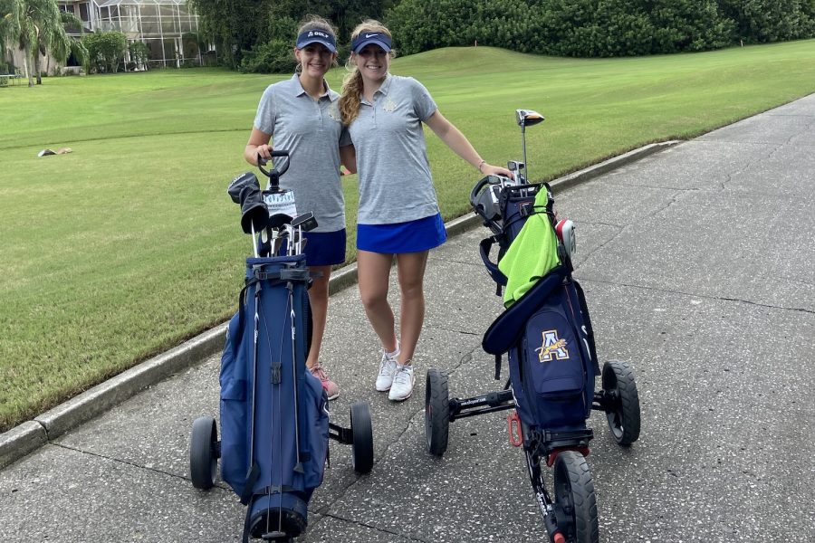 Golf team members Sadie Campbell ('22) and Taylor Schweitzer ('23) waiting on TPC's hole three.