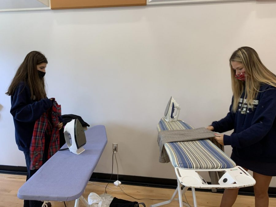 Lauren Donofrio ('23) and Emmy Growcock ('23) ironed clothes that had been washed before in this photo.