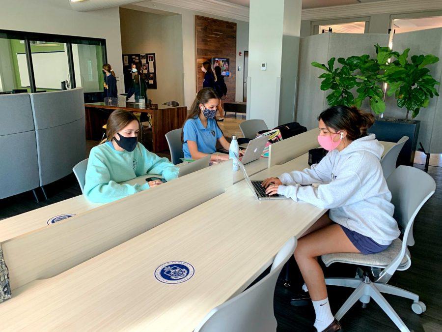 Juniors Maria Alvarez, Ashley Canal, and Caro Guixens work at a socially-distanced table.
