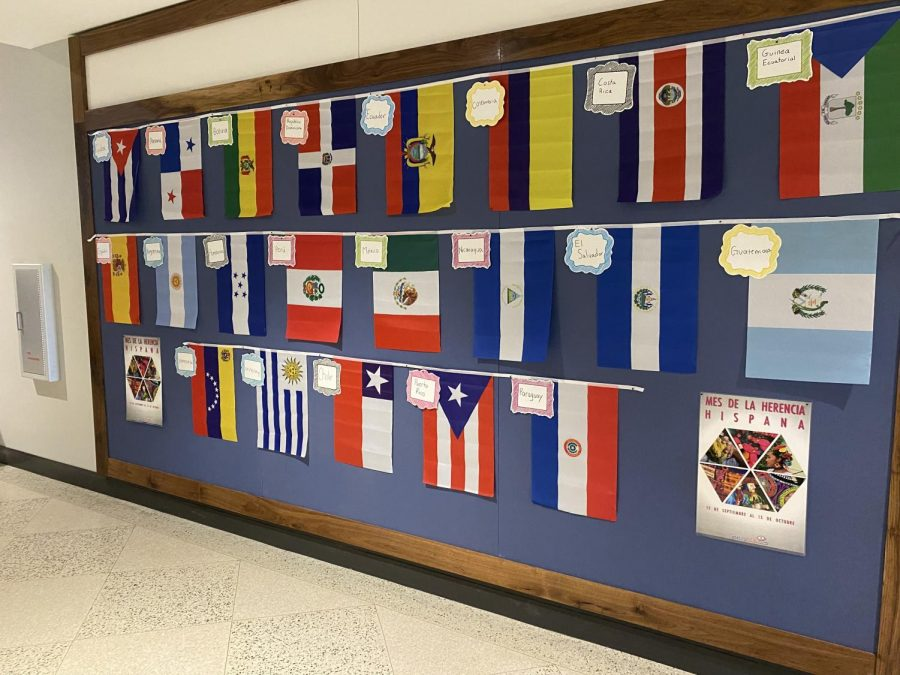 In the third floor, there is a bulletin board filled with labeled  flags from different hispanic countries.